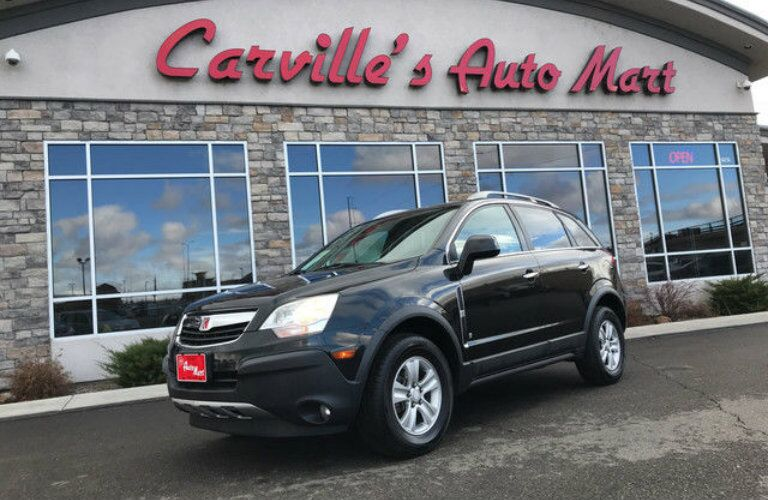 Black Saturn VUE SUV parked in front of Carville's Auto Mart exterior