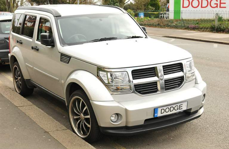 "White Dodge Nitro SUV parked on street in front of ""Dodge"" sign"
