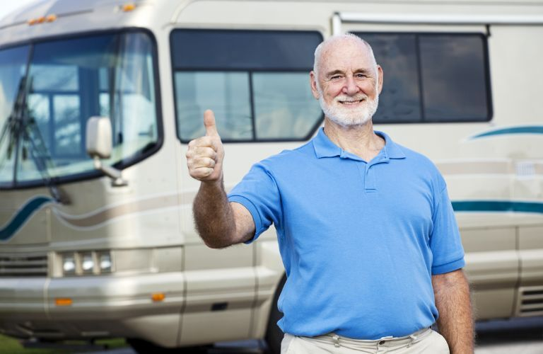 Man in front of a motorhome give a thumbs up