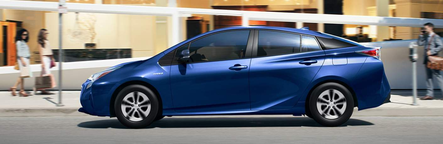 Profile shot of blue 2018 Toyota Prius driving down city street with two women walking past
