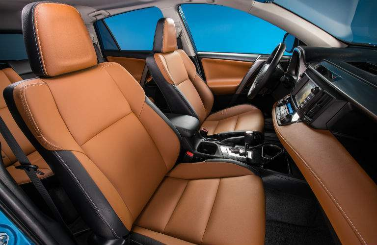 Leather-stitched front seat of 2018 Toyota RAV4 with dashboard and steering wheel prominent