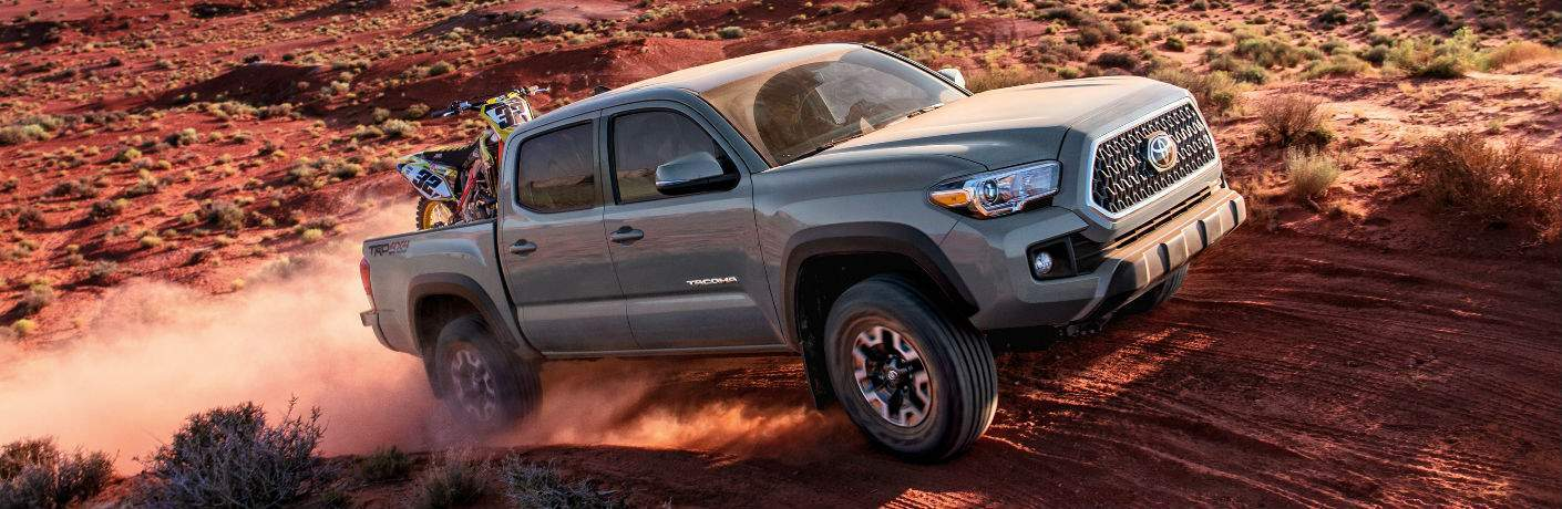 Profile shot of 2018 Toyota Tacoma driving up dirt road with desert landscape in background