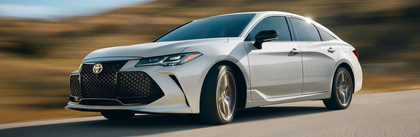 White 2019 Toyota Avalon Hybrid driving on waterfront road