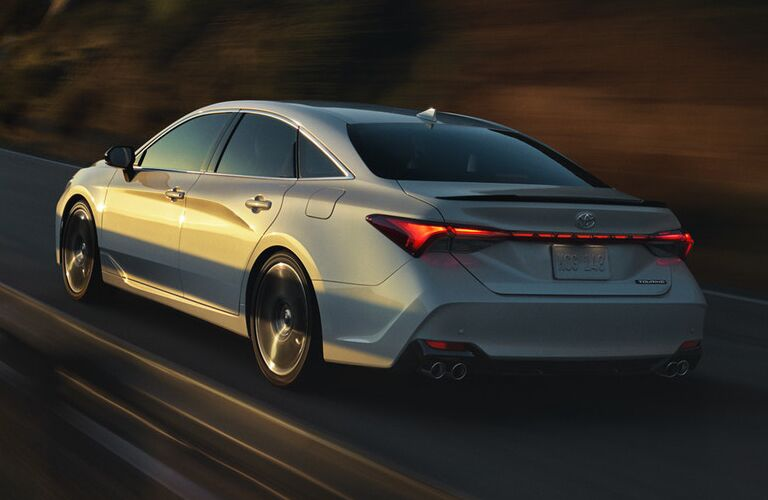 Rear shot of silver 2019 Toyota Avalon driving on mountainous road