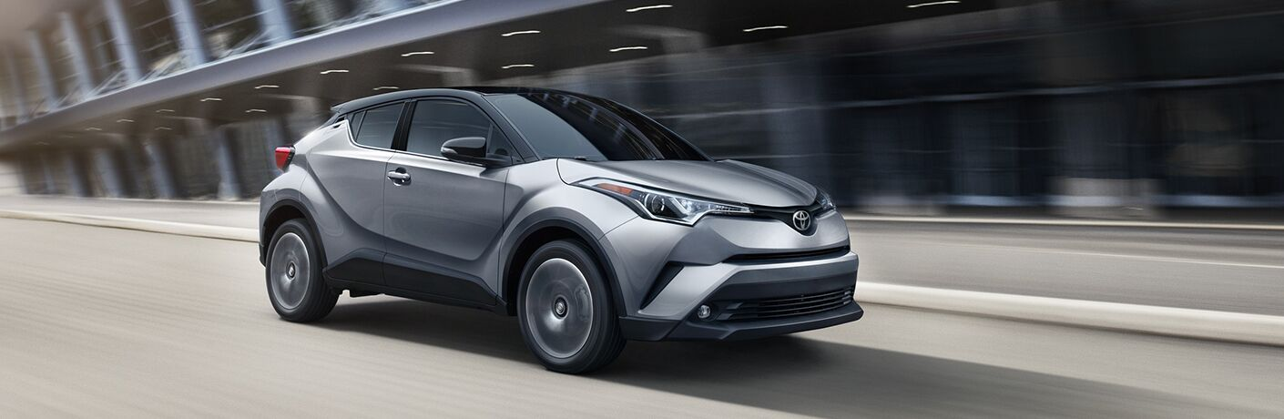 Silver 2019 Toyota C-HR driving on city road in front of modern styled business building