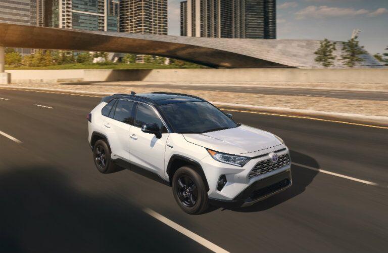 White 2019 Toyota RAV4 driving on city road