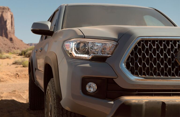 close up front shot of silver toyota tacoma in desert
