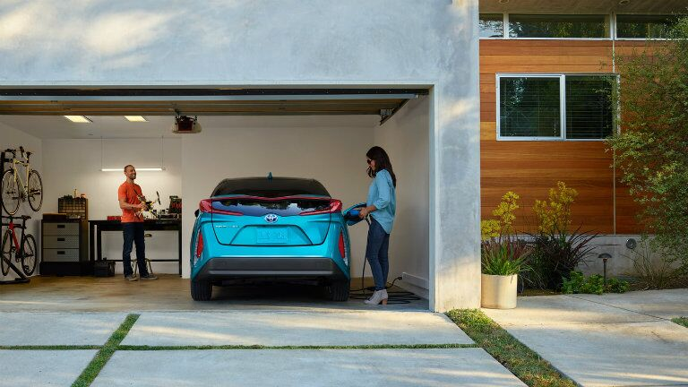 Man and woman charging a 2018 Toyota Prius Prime