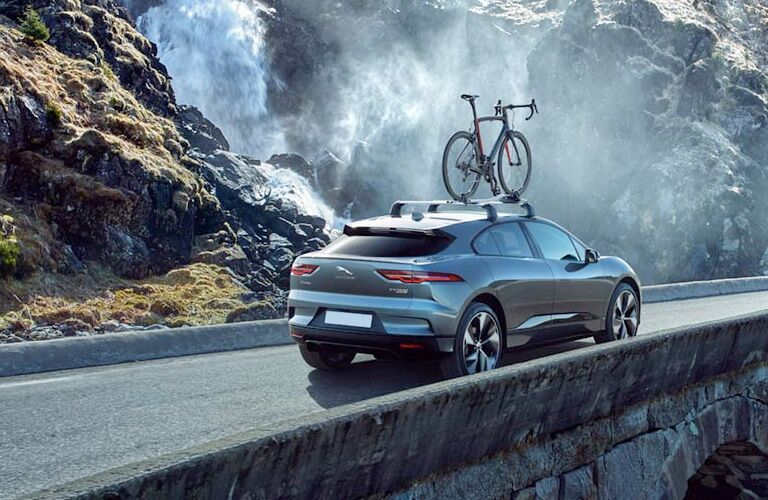 Gray 2019 Jaguar I-PACE Rear Exterior Driving on Mountain Road Next to Waterfall with Bike on the Roof