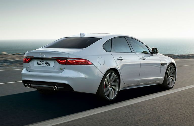 White 2019 Jaguar XF Sedan Rear Exterior on a Coast Road