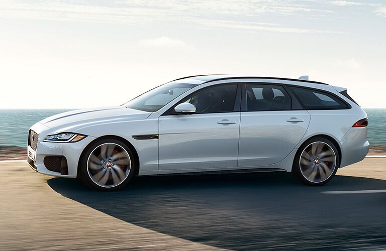White 2020 Jaguar XF Sportbrake Side Exterior on a Coast Road