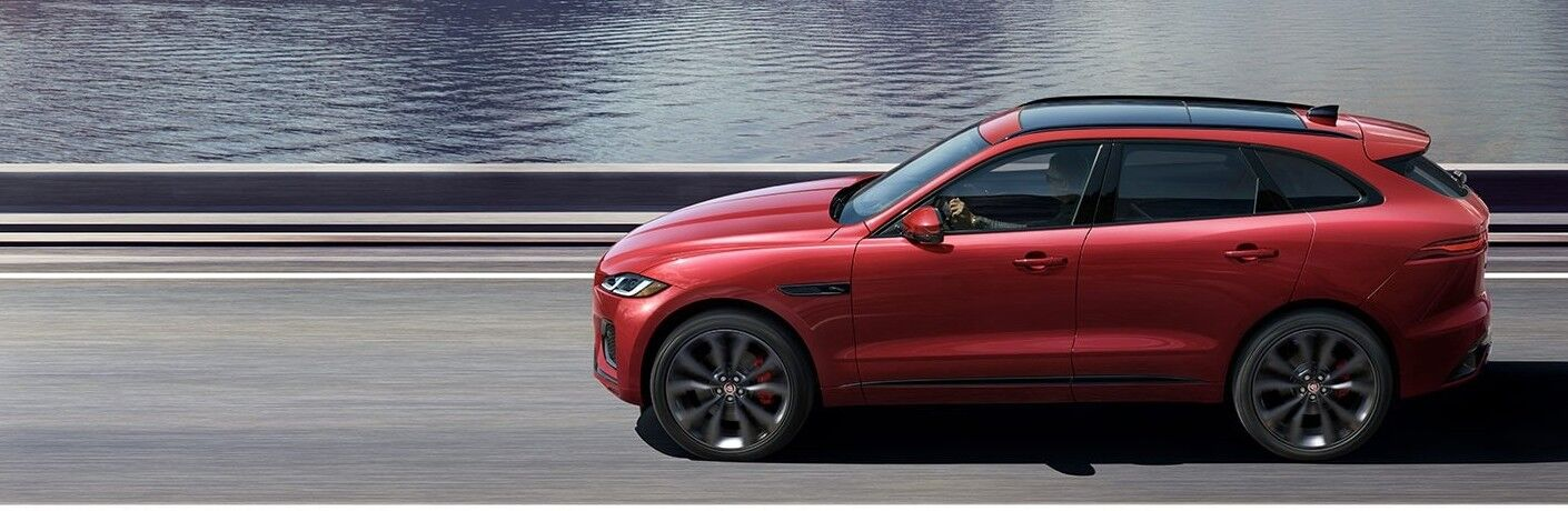 2021 Jaguar F-PACE going down the road next to water