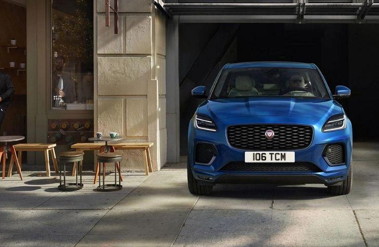 A blue 2022 Jaguar E-Pace parked next to a cafe.