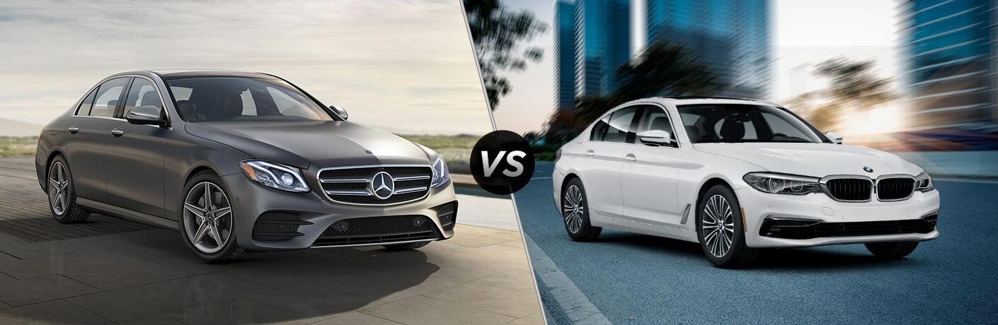 2019 MB E 300 sedan exterior front fascia and passenger side vs 2019 BMW 530i sedan exterior front fascia and passenger side on blurred city background