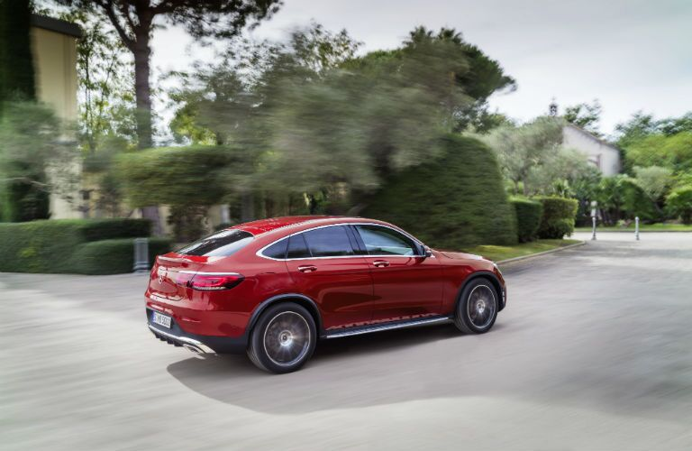 2020 MB GLC Coupe exterior back fascia and passenger side going fast on blurred suburban road with shrubbery