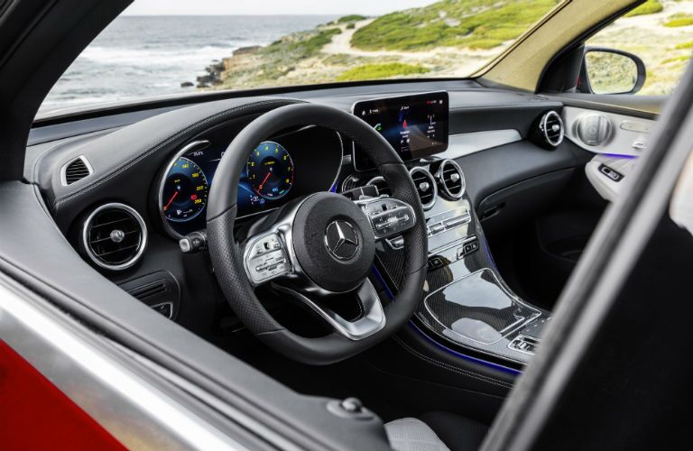 2020 MB GLC Coupe exterior looking into front cabin steering wheel and dashboard with ocean in windshield