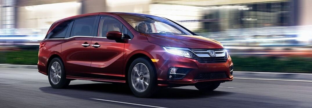 Image of a red 2019 Honda Odyssey driving on a city street at night.