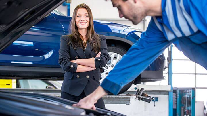 Image of a woman standing in front of a mechanic working on her car.