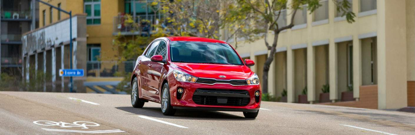 Red 2018 Kia Rio driving down the street