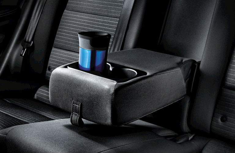 cupholder on fold down arm rest in rear seat of 2018 kia forte black leather seating