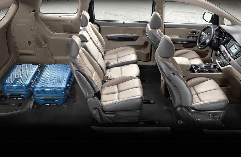 Storage in 2018 kia Sedona shown with two suitcases in way back and middle row three seats