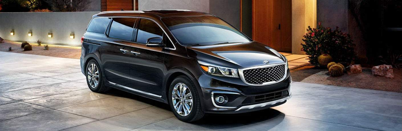2018 kia Sedona in black exterior parked on cement in front of nice home