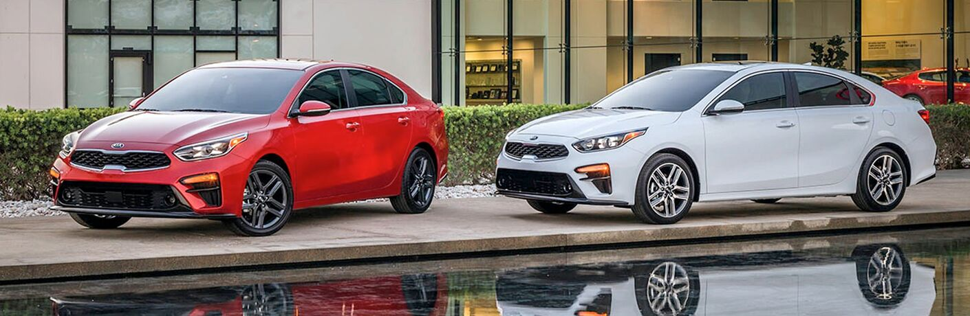 2019 kia forte in both red and white parked on edge of swimming pool