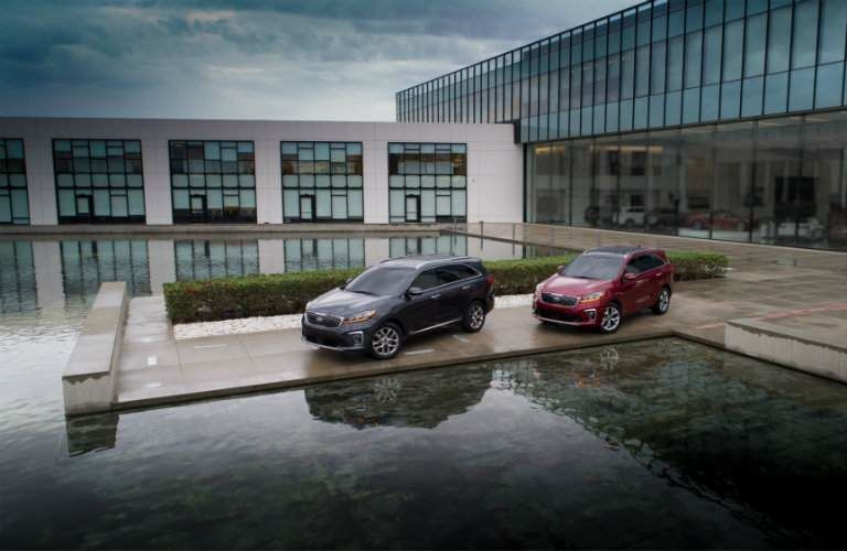 Two, 2019 Kia Sorento models near a modern building and a pool