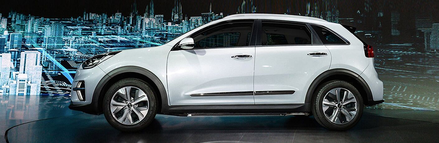 left side of white kia niro, hologram of city in background