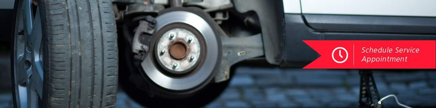 closeup of brake on vehicle with Schedule Service Appointment text overlaid