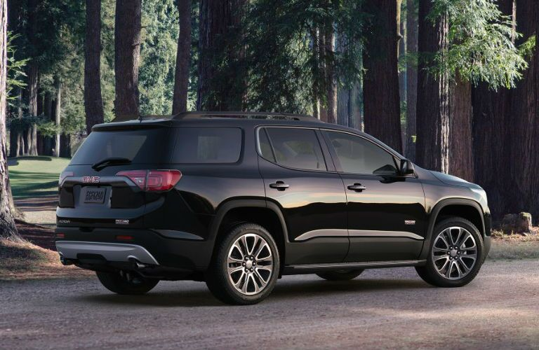 Black 2017 GMC Acadia in the woods