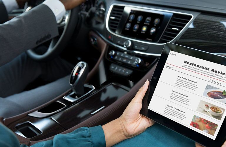 2019 Buick LaCrosse Avenir interior with someone using a tablet and the Wi-Fi hotspot