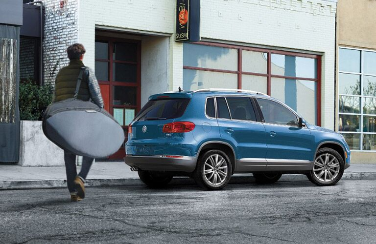 man with surfboard approaching blue 2017 VW Tiguan