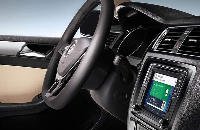 Interior of the 2018 Volkswagen Jetta with a focus on the steering wheel and screen display with navigation