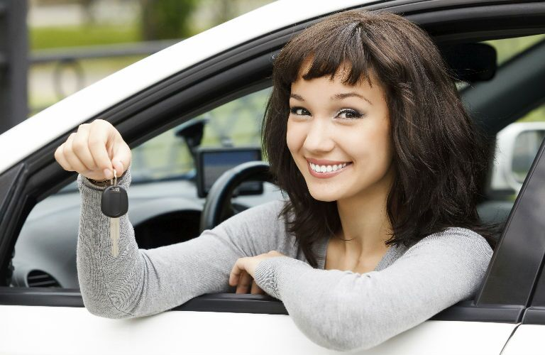 young woman holding car key out car window