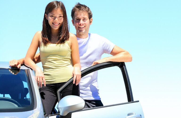 young couple standing at car on sunny day