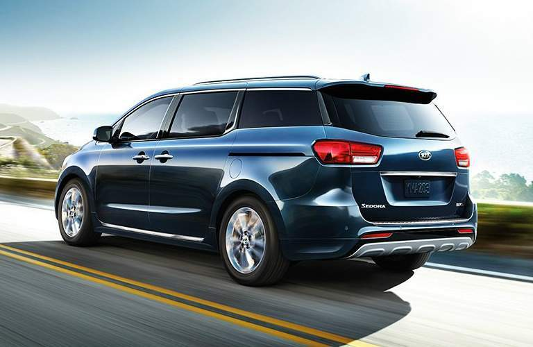 blue 2018 Kia Sedona driving on windy road