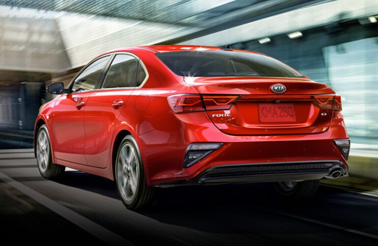 Red 2020 Kia Forte driving down a city street.