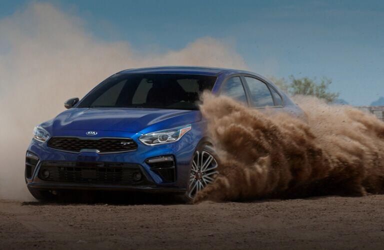 Blue 2020 Kia Forte kicks up a cloud of dust and looks really cool.