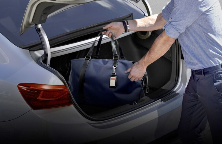 Man loads a bag into the trunk of a 2020 Kia Forte.