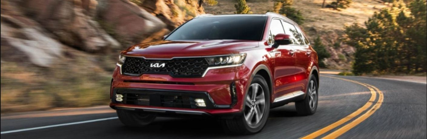 A red 2022 Kia Sorento Hybrid driving on a highway at high speeds