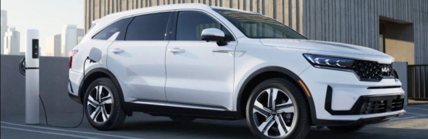 A white-colored 2022 Kia Sorento Plug-in Hybrid getting charged
