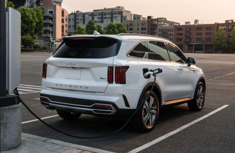 Rear view of a white-colored 2022 Kia Sorento Plug-in Hybrid getting charged