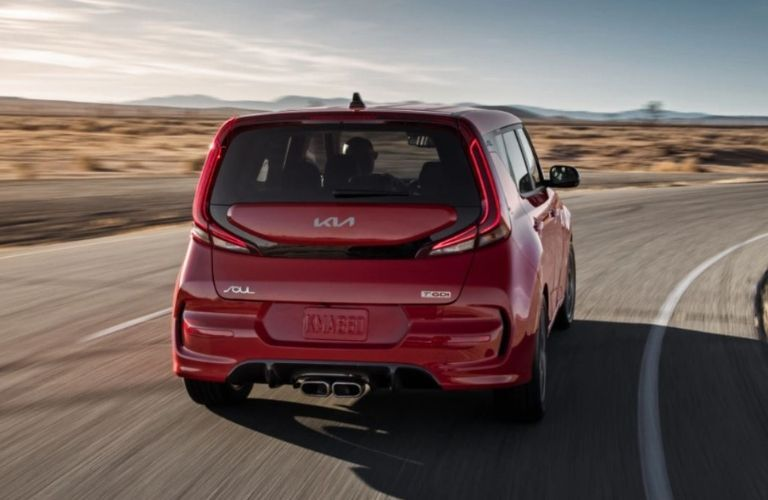 Rear view of a red Kia Soul on a desert road