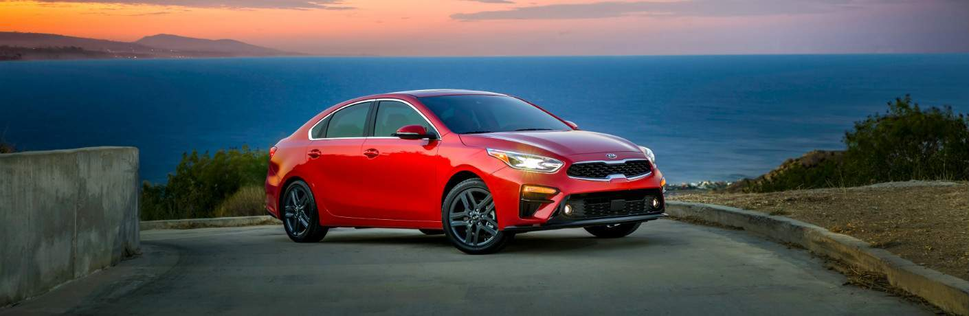 red 2019 Kia Forte parked on slope overlooking water body
