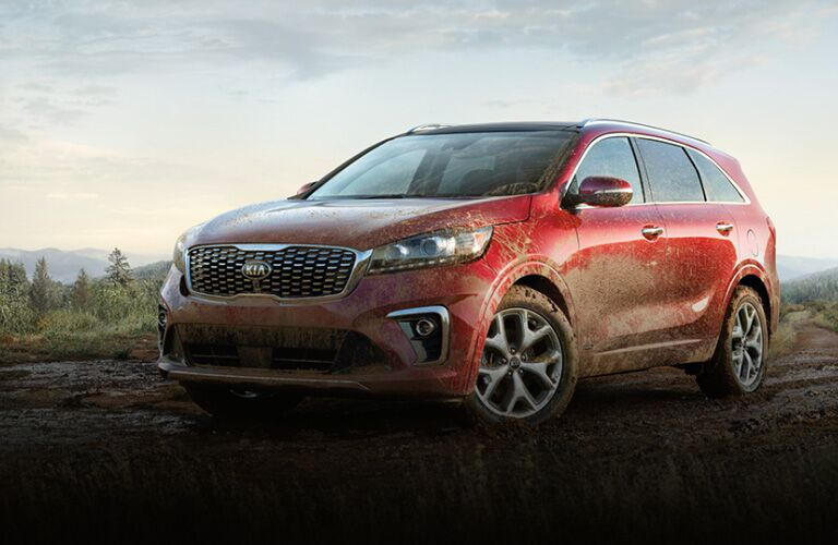 2020 Kia Sorento red exterior front driver side parked in field covered in mud