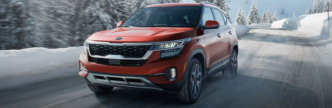 2021 Kia Seltos red exterior front driver side driving in winter on snowy road