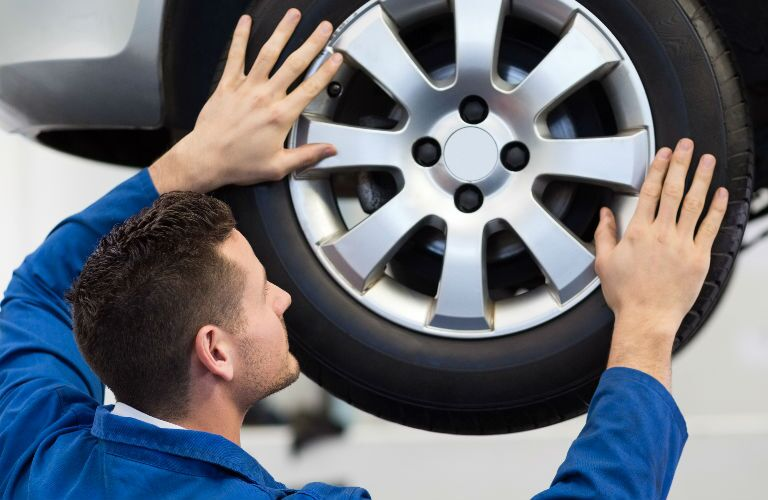 Technician Facing Tire Adjusting Alignment