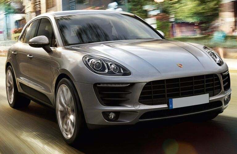 Exterior view of a silver 2017 Porsche Macan driving down a city street