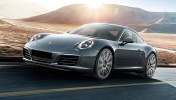 Exterior view of a green 2017 Porsche 718 driving down the highway
